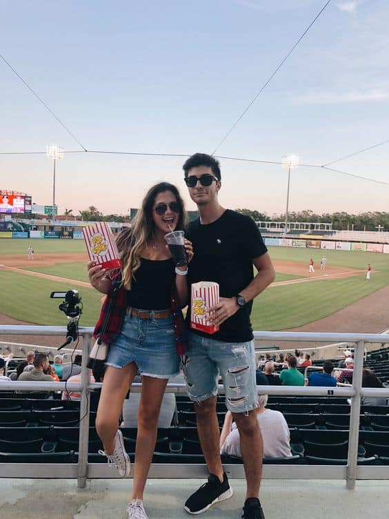 A couple at a game holding popcorn and drinks
