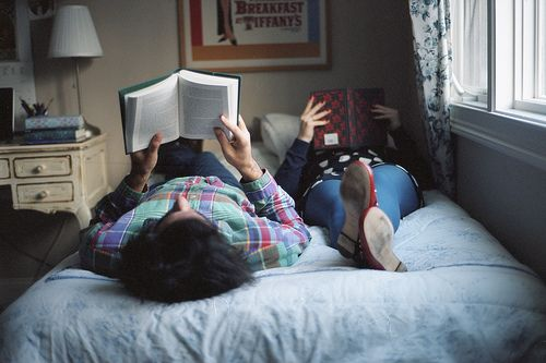 A couple lying on the different sides of a bed reading books