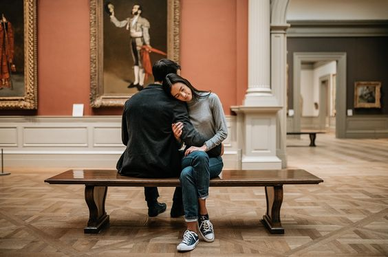 A couple sitting in a museum facing opposite sides