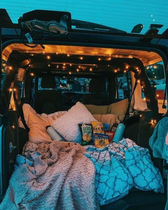A trunk of a car setup with lights, blankets, and snacks for a drive-in movie