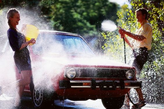 A couple having fun with water while washing a car