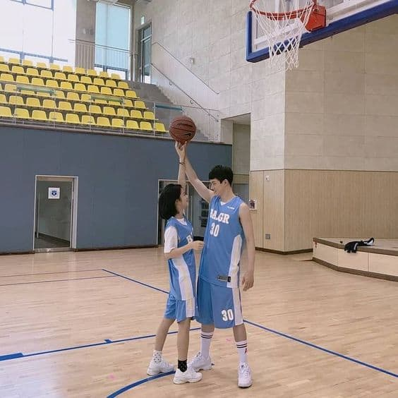 A couple at a basketball court playing basketball