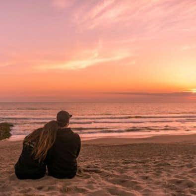 A couple watching the sunset at the beach