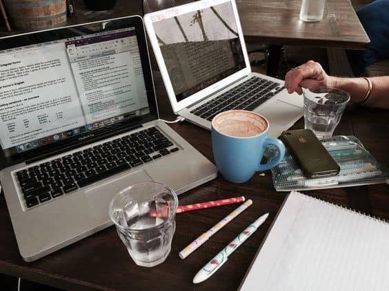 Two laptops side by side with coffee and pens