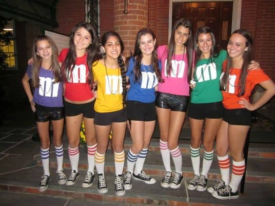 A group of girls wearing 'm' shirts in different colors
