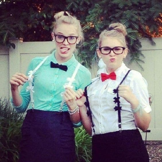Two girls dressed as nerds in glasses, fully buttoned shirts and bow ties