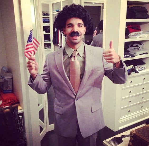 A guy dressed as Borat holding the American flag