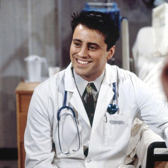 A smiling guy in a doctor's outfit