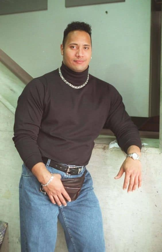 Dwayne Johnson in jeans, a fanny pack, turtle neck, and gold chain