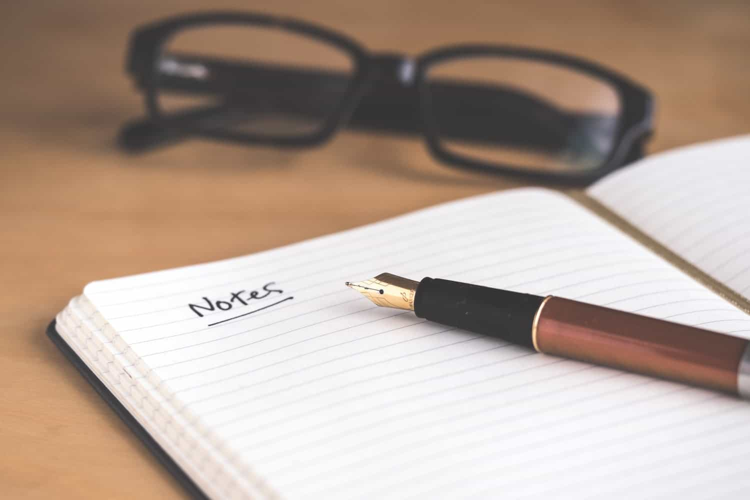 A Notebook with a pen and reading glasses