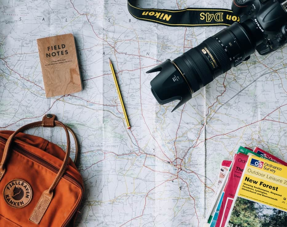 A camera, books and a bag on a map