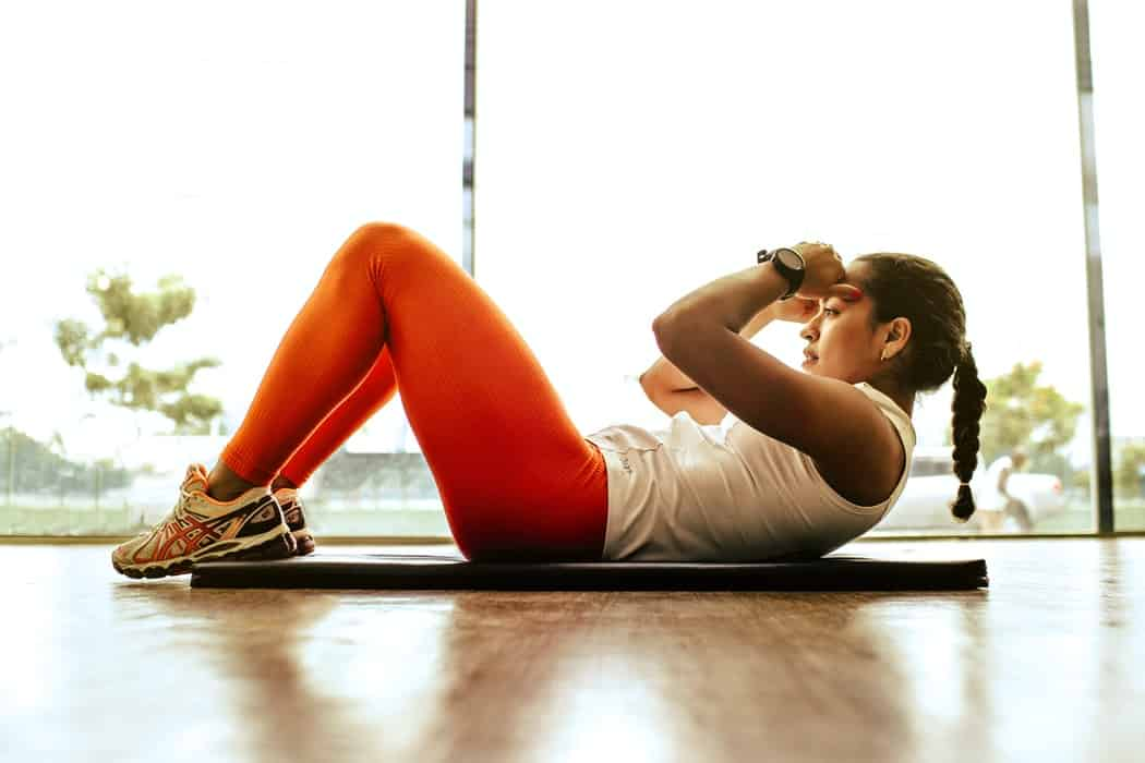 A woman doing situps on a yoga mat
