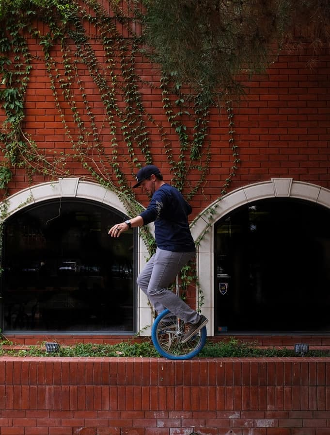 A man riding a unicycle near a wall