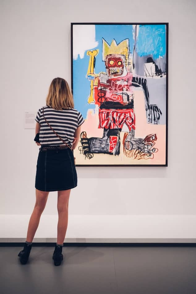 A woman in a black and white striped shirt and a denim skirt looking at a painting