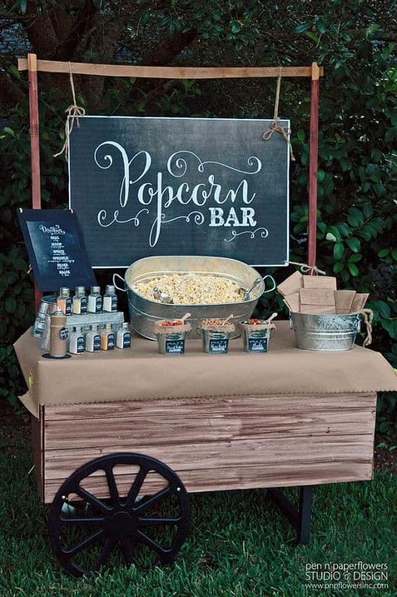 Popcorn and different toppings in front of a Popcorn Bar sign