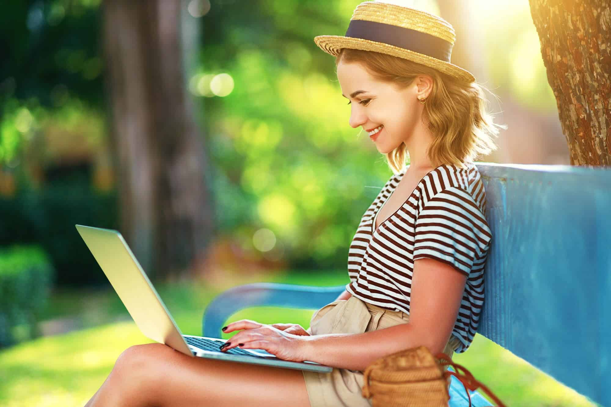 Female college student sitting on a bench in a park smiling at her computer