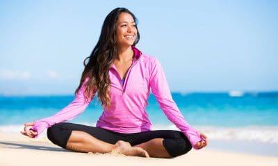 A woman sitting on a beach meditating