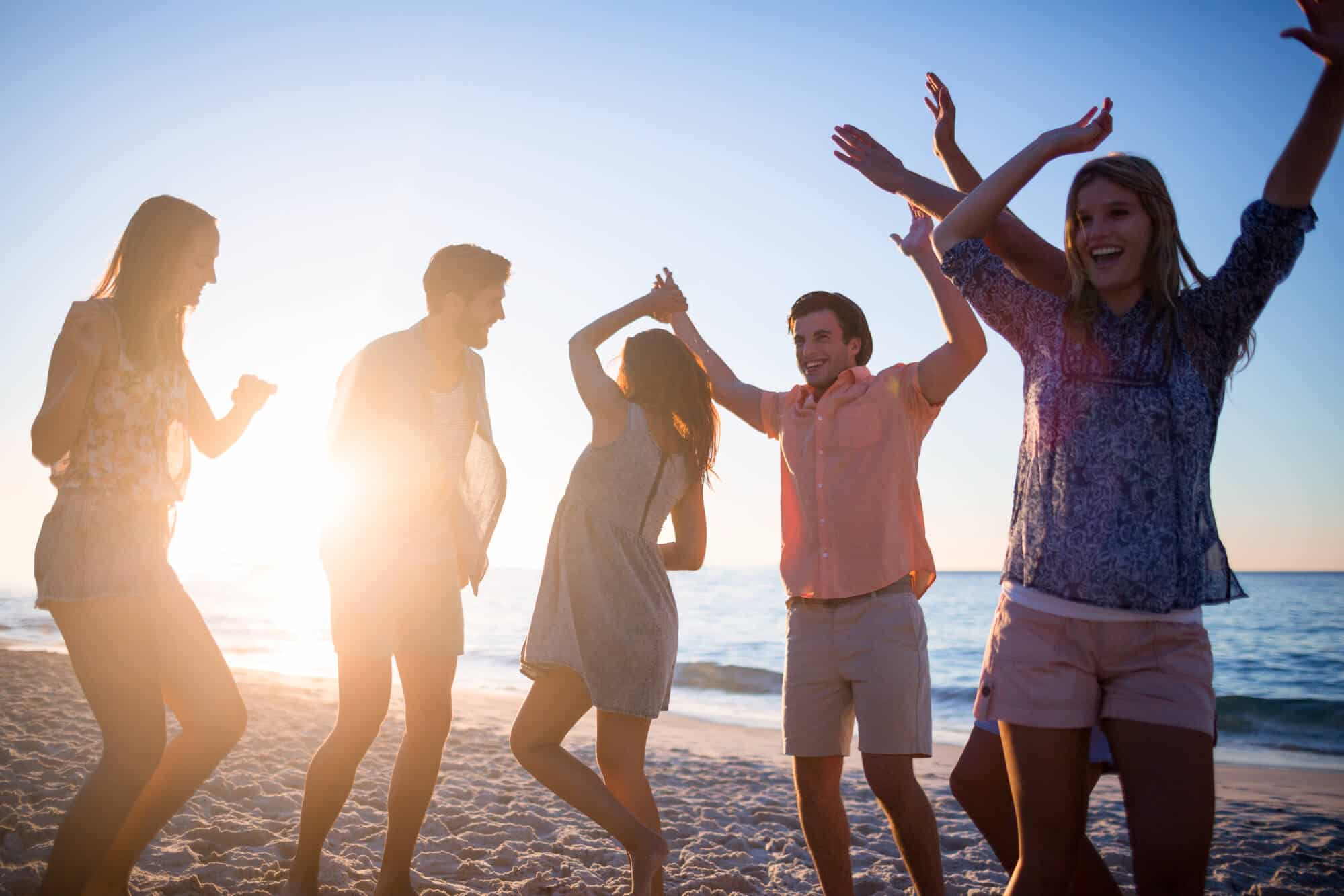 Five college students dancing during summer on the breach