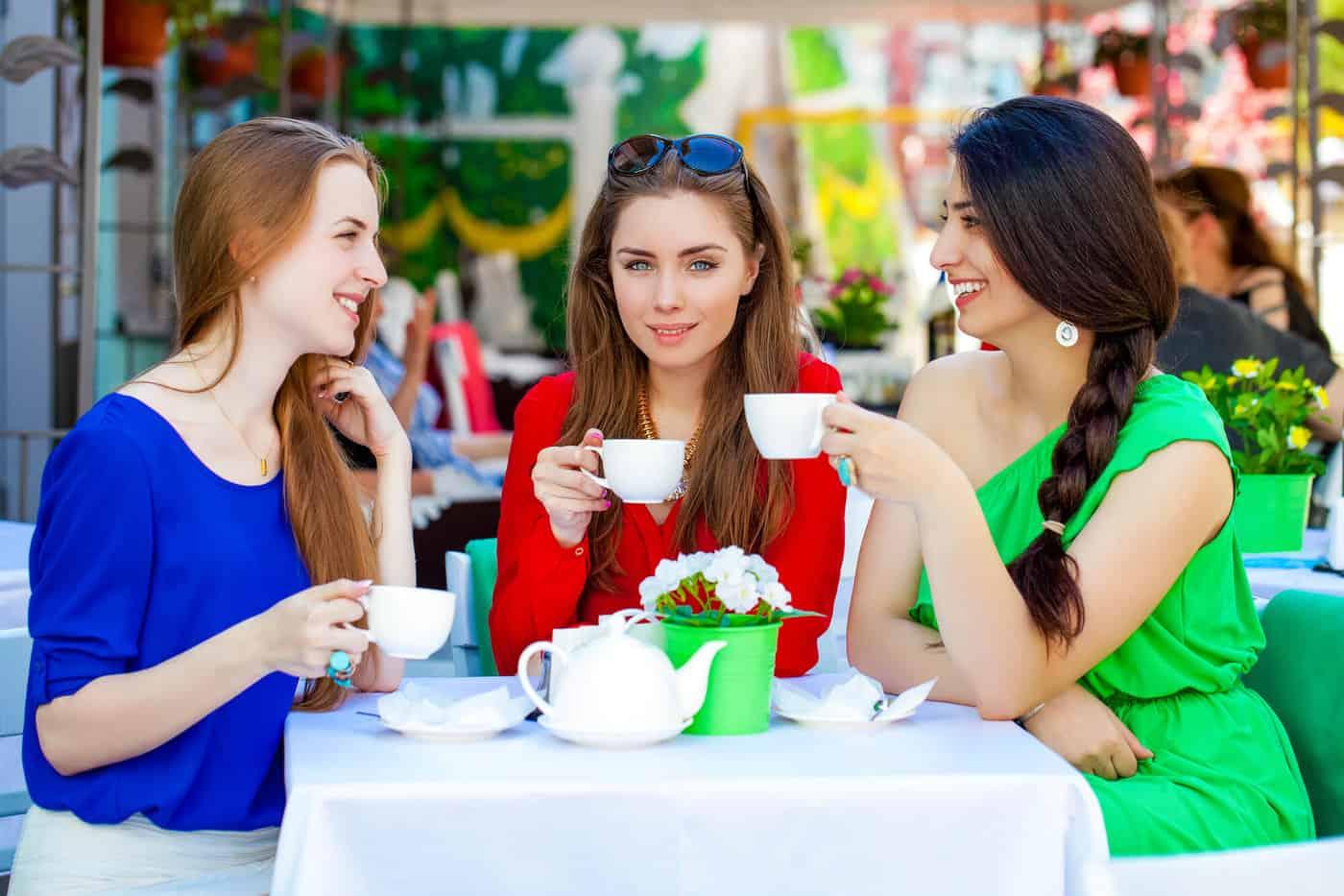 Three classy women having tea at a table