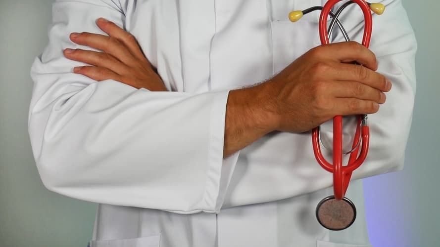 A doctor holding a red sthethscope