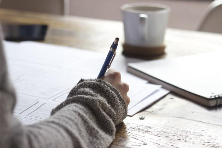 A person writing besides a cup of coffee