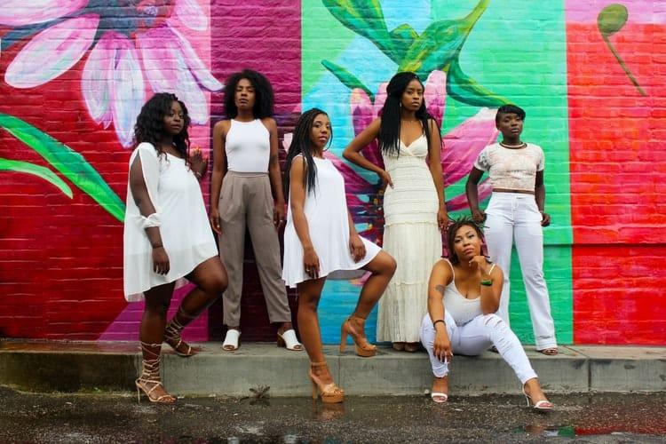 Six well dressed black women in front of a street art