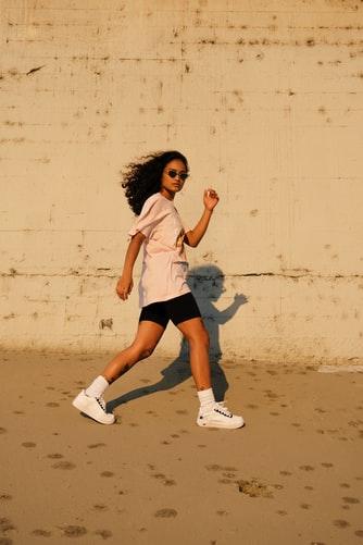 A woman walking near a wall