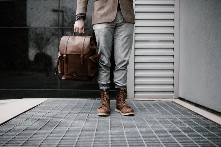 A person holding a brown leather backpack