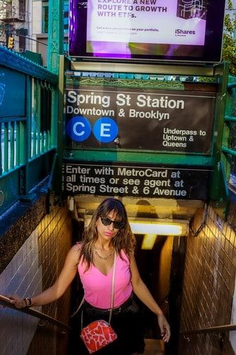 A well dressed woman in front of a subway station