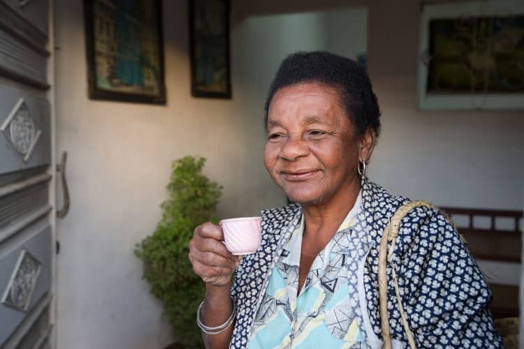 An older woman holding a cup