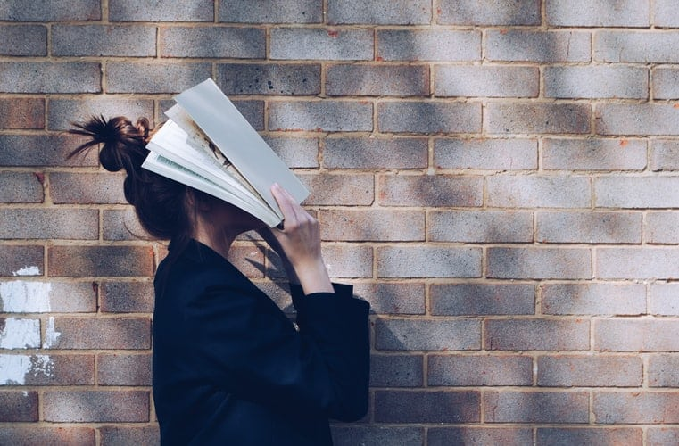 A woman near a wall covering her face with an open book