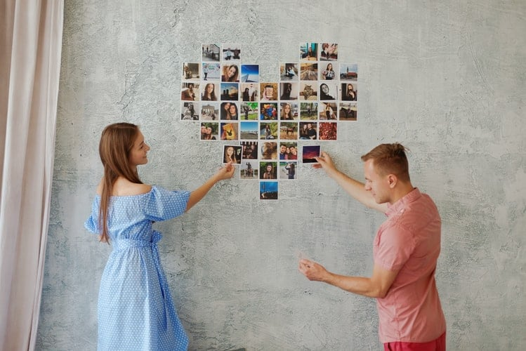 A girl in a blue dress and a guy in a pink shirt pasting photos on a wall in the shape of a heart