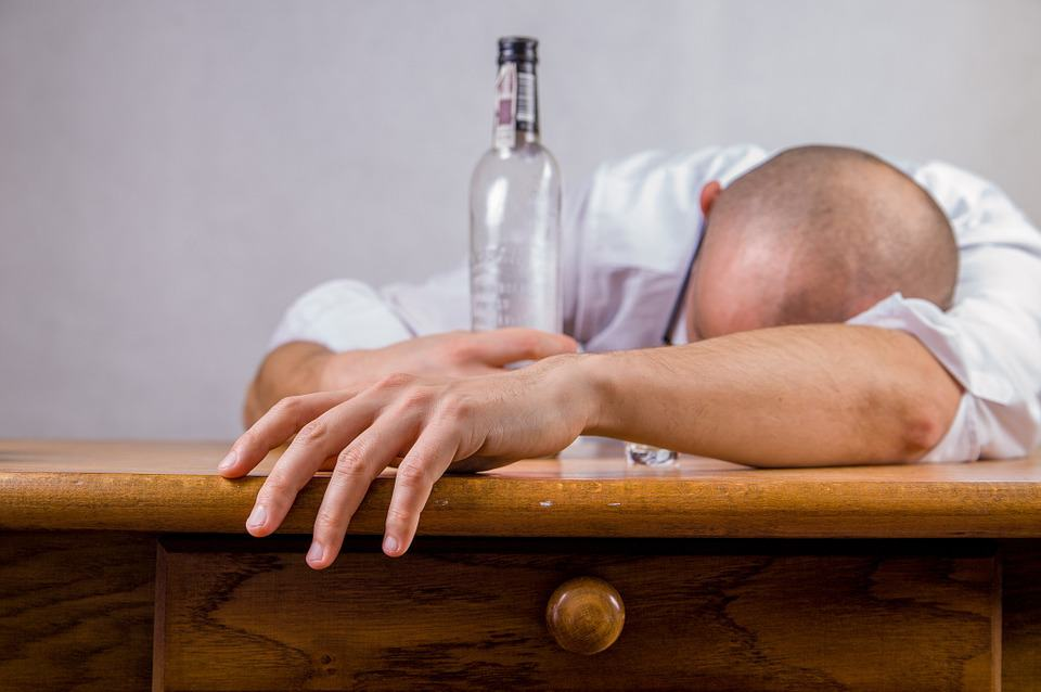 A man facing down on a table holding a liquor bottle in his hands
