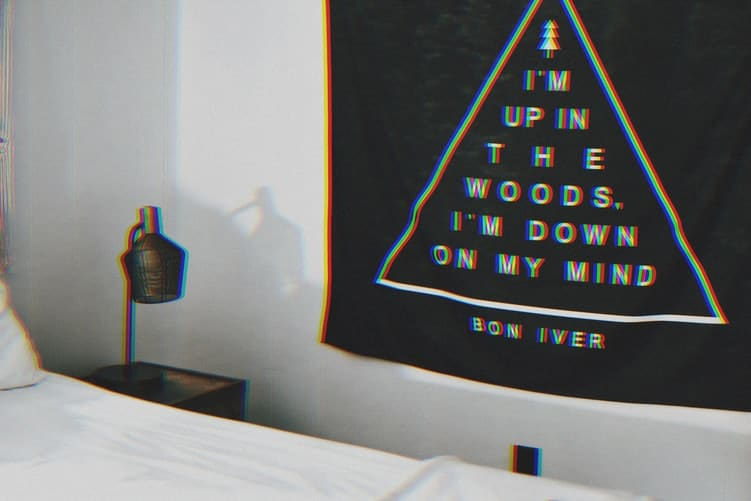 A poster up on the wall next to a bed