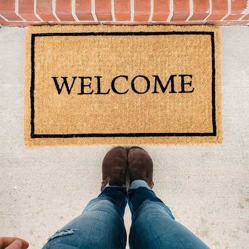 A person standing in front of a 'welcome' mat