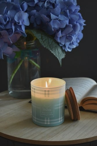 A lit candle besides an opened book a vase of blue flowers