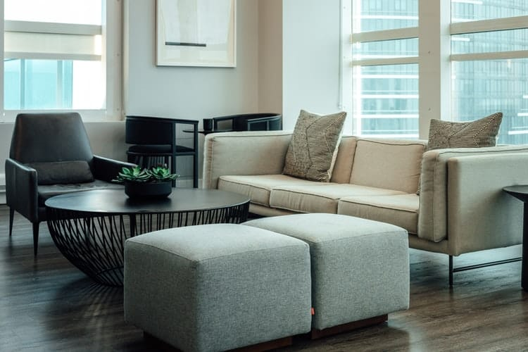 A gray sofa set besides a beige couch and a round table in the middle