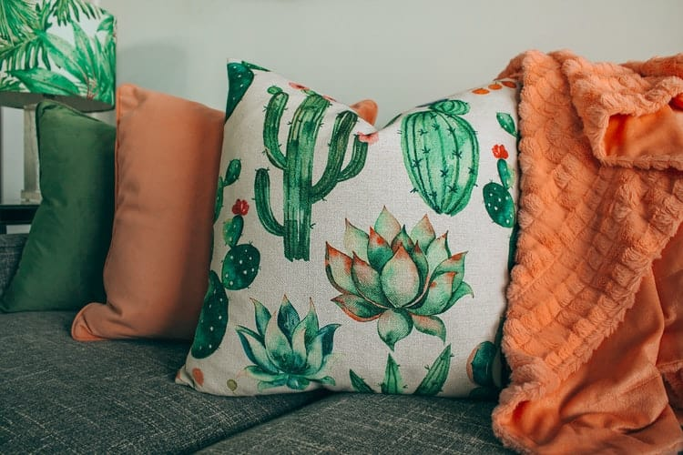 Green, orange and tropical colored throw pillows on a couch