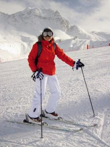 Woman skiing wearing a red jacket and white pants holding polls