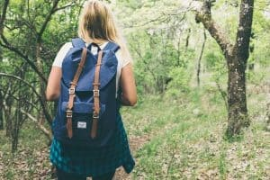 A woman hiking in the forrest with a backpack on