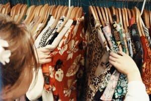 Girl looking through a shirt clothing rack