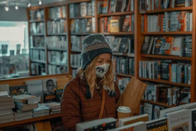 girl wearing a hat and mask in a thrift shop
