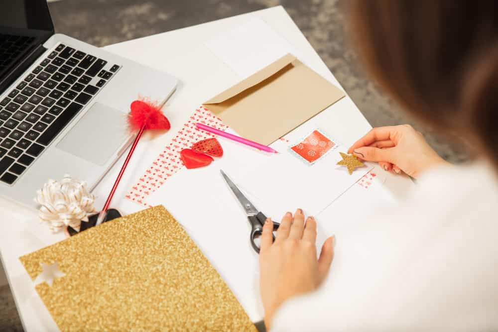 A person scrapbooking with papers and markers on the desk