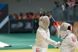 Two fencers in the middle of a competition wearing fencing gear