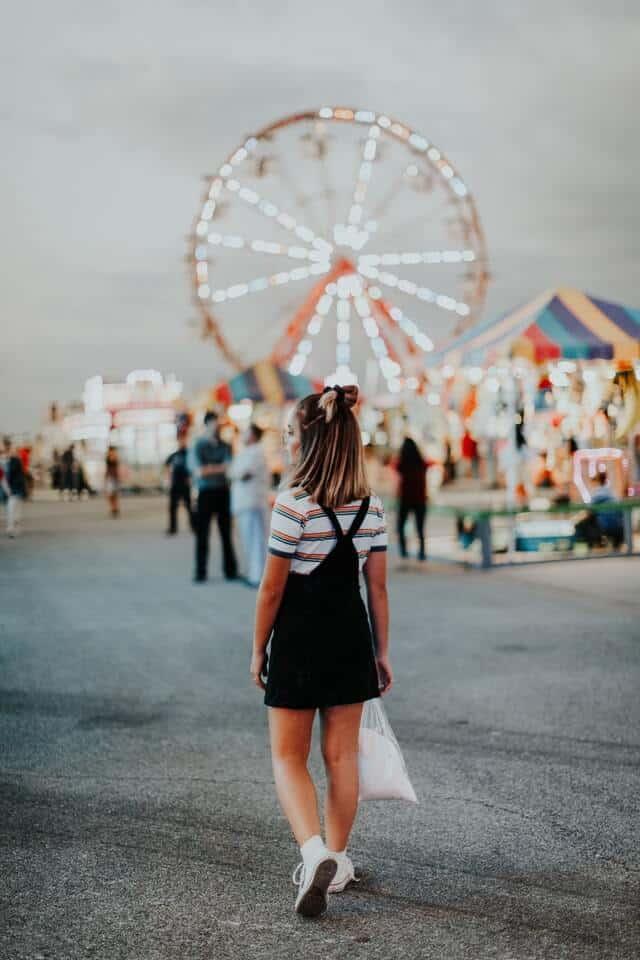 A girl walking toward a carnival