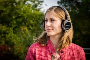 A woman wearing headphones outside with a red jacket