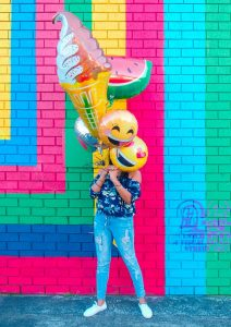 girl in front of a colorful wall holding balloons