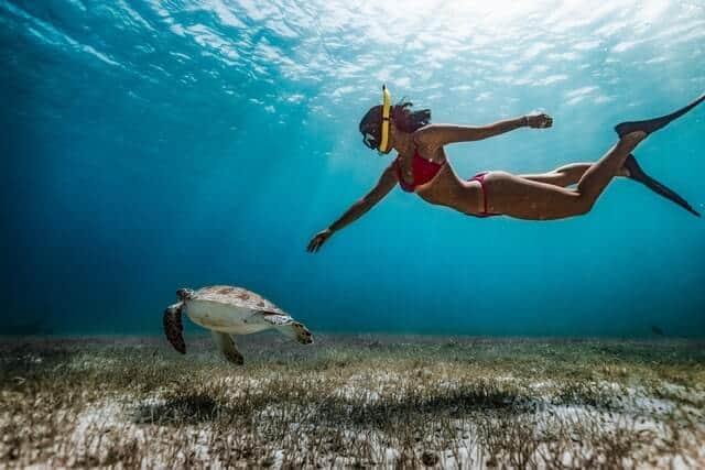 a girl snorkeling in blue water