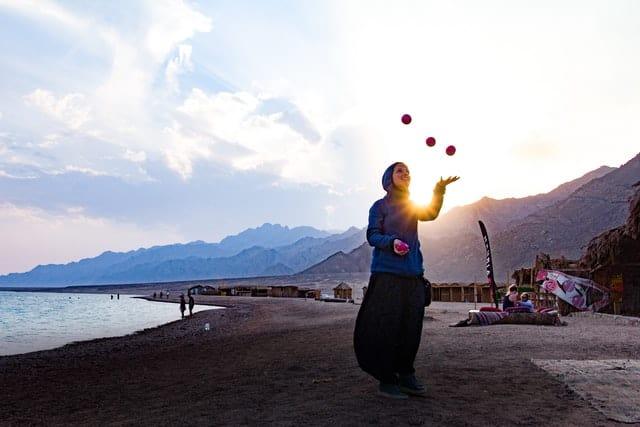 A woman juggling on a beach