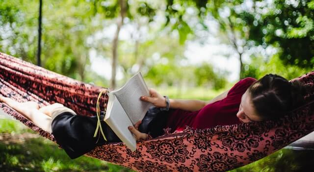 Girl laying in a hammock reading a book in the shade